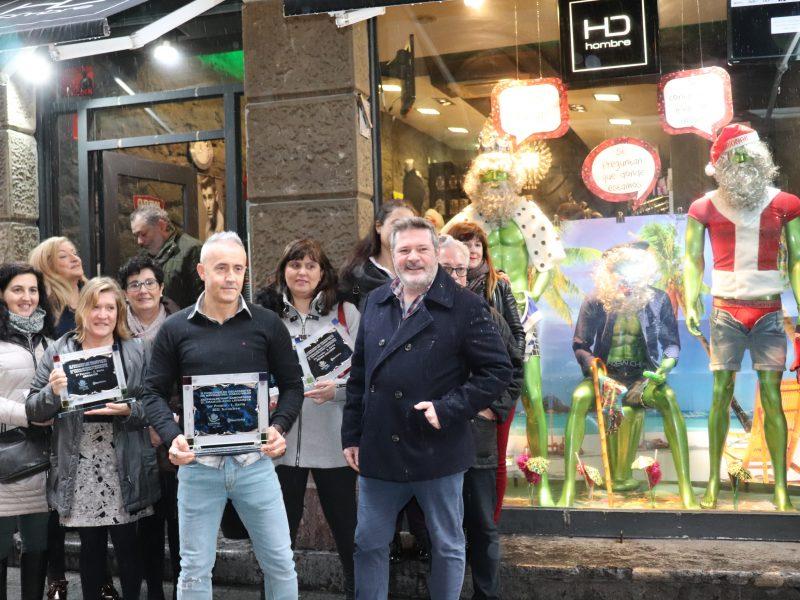 Los premiados, junto al escaparate ganador.